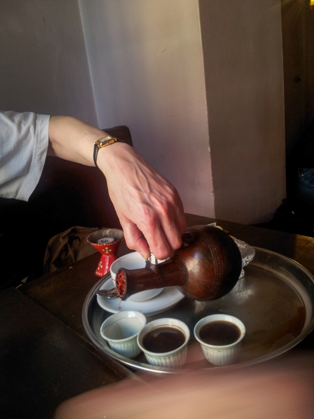 Pouring coffee from traditional Eritrean pot