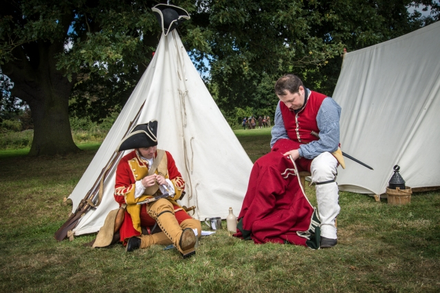 Soldiers in period costume outside tent, sewing.