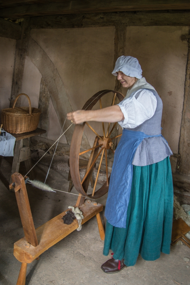 Woman in 18th centry costume at spinning wheel